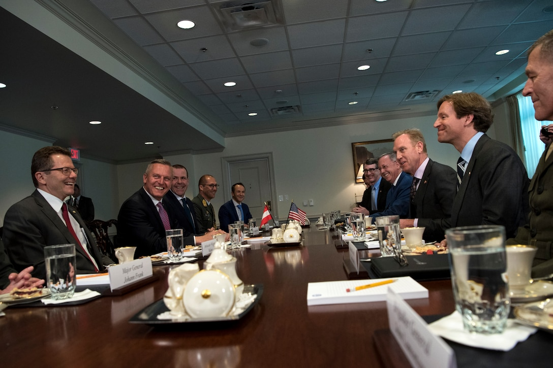 Acting Defense Secretary Patrick M. Shanahan sits at at table with a group of people.