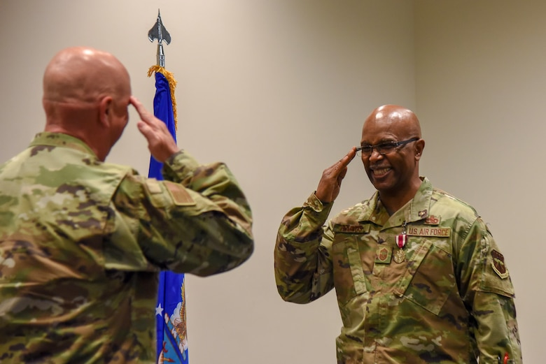 Chief Master Sgt. Marshall O. Harris Jr., 403rd Maintenance Group quality assurance superintendent at Keesler Air Force Base, Miss., salutes Col. Jay Johnson, 403rd MSG commander, after receiving a coin during his retirement ceremony at Roberts Maintenance Facility April 6, 2019. (U.S. Air Force photo by Senior Airman Kristen Pittman)