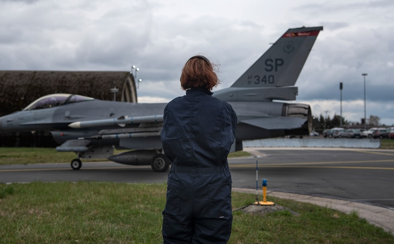 U.S. Air Force Staff Sgt. Stephanie Gillie, 52nd Security Forces Squadron investigator, watches an F-16 Fighting Falcon taxi at Spangdahlem Air Base, Germany, April 3, 2019. Gillie volunteered to participate in the 52nd Aircraft Maintenance Squadron Crew Chief for a Day program for a better understanding of flightline operations. She had never been on a flightline or near fighter jets before this opportunity. (U.S. Air Force photo by Airman 1st Class Valerie Seelye)