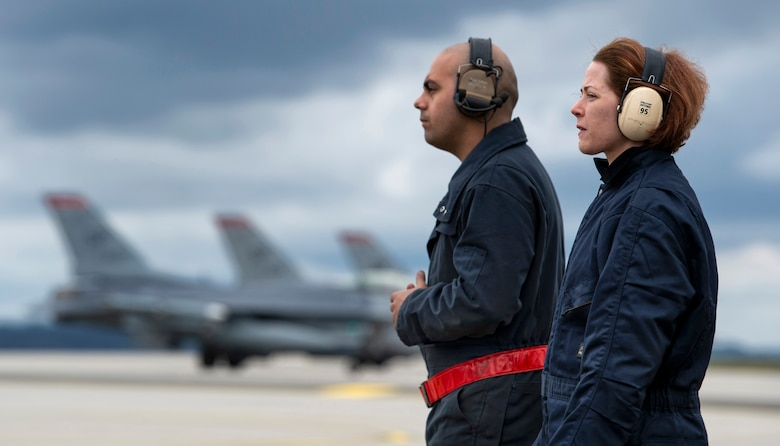 U.S. Air Force Staff Sgt. Stephanie Gille, 52nd Security Forces Squadron investigator, right, and Senior Airman Jose Pagan, 52nd Aircraft Maintenance Squadron assistant dedicated crew chief, left, observe a final F-16 Fighting Falcon inspection at Spangdahlem Air Base, Germany, April 3, 2019. Gillie shadowed Pagan for his entire shift as part of the 52nd AMXS Crew Chief for a Day program. The program is open to all Airmen, but encourages staff sergeants and below to participate for a better understanding of flightline operations. (U.S. Air Force photo by Airman 1st Class Valerie Seelye)