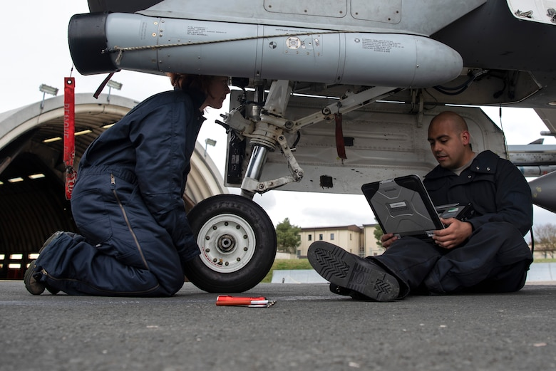 U.S. Air Force Staff Sgt. Stephanie Gillie, 52nd Security Forces Squadron investigator, left, observes Senior Airman Jose Pagan, 52nd Aircraft Maintenance Squadron assistant dedicated crew chief, right, as he inspects F-16 Fighting Falcon landing gear at Spangdahlem Air Base, Germany, April 3, 2019. Gillie, who had never been on a flightline before, volunteered for the 52nd AMXS Crew Chief for a Day program. She learned how inspections are performed and how to prepare an aircraft for launch. (U.S. Air Force photo by Airman 1st Class Valerie Seelye)