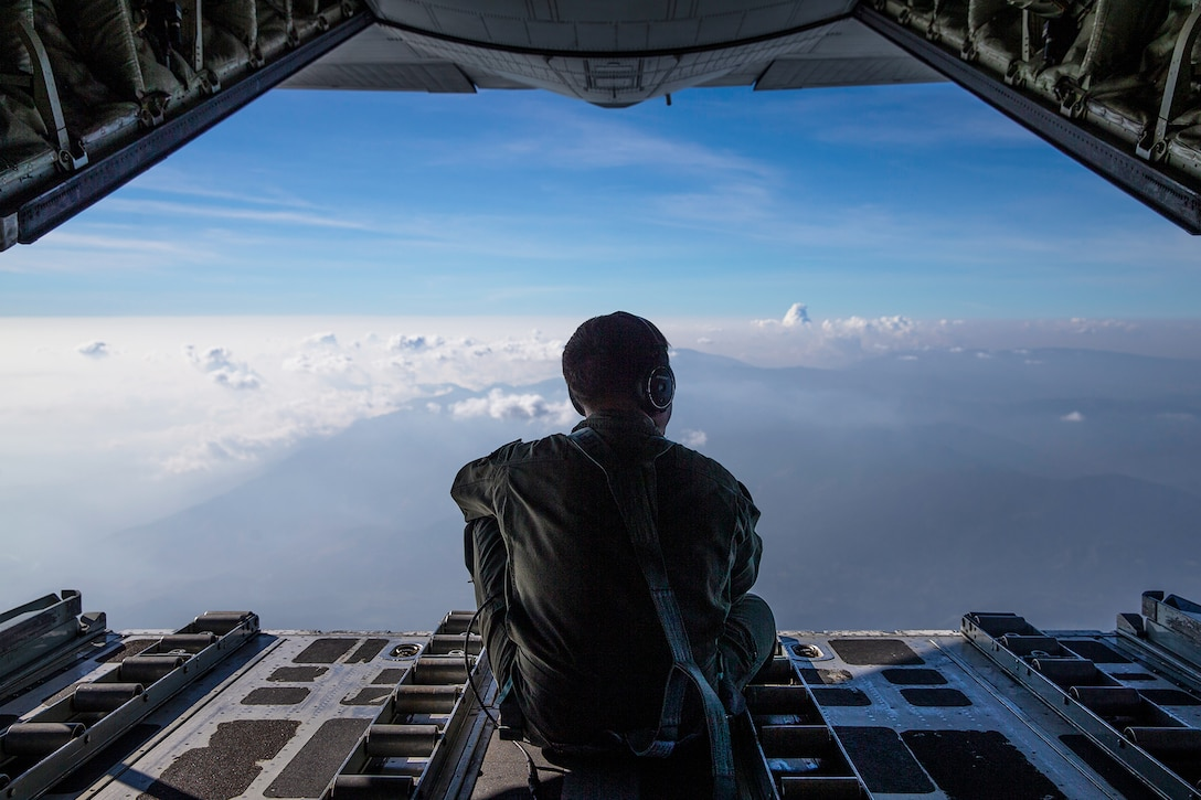 A Marine looks out from an aircraft.