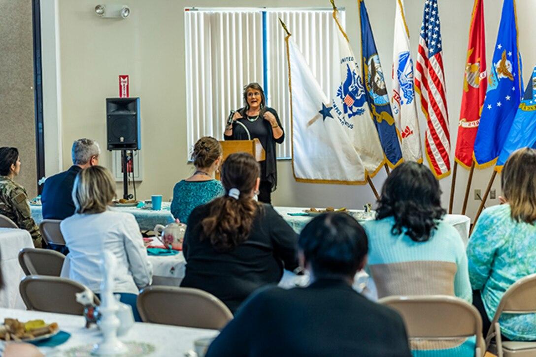 Keynote speaker speaks next to flags to a full room