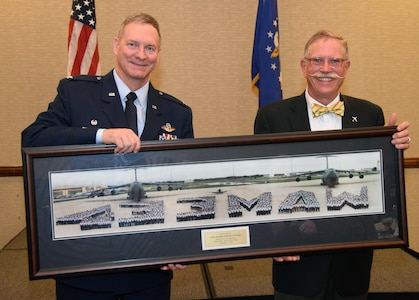 Col. Terry McClain, 433rd Airlift Wing commander, is presented with a vintage 433rd Military Airlift Wing panoramic photo from 1991 by Steve Richmond, an honorary commander alumni and president of Pizza Hut of San Antonio, April 6 at a northwest San Antonio hotel. Seventeen honorary commanders were inducted at the annual event.