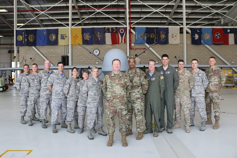 Members from the 163rd Attack Wing, California Air National Guard, March Air Reserve Base, pose for a photo in front of an MQ-9 Reaper remotely piloted aircraft here with leaders from the 452nd Air Mobility Wing and U.S. Air Force Lt. Gen. Richard Scobee, commander of Air Force Reserve Command, and U.S. Air Force Chief Master Sgt. Timothy White, AFRC command chief, on April 6, 2019. AFRC senior leadership toured March ARB to learn about the 452nd AMW's mission, capabilities and challenges as part of a three-day unit visit.
