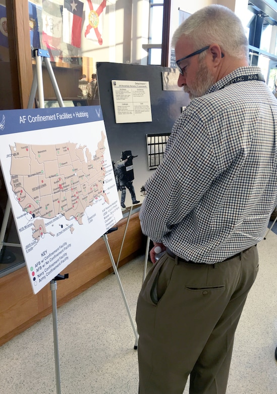 Joe Hart of the Air Force Civil Engineer Center views a security forces display in the lobby of the Pfingston BMT Reception Center at Joint Base San Antonio-Lackland during a break in the Installation and Mission Support Weapons and Tactics Conference outbriefs April 10.