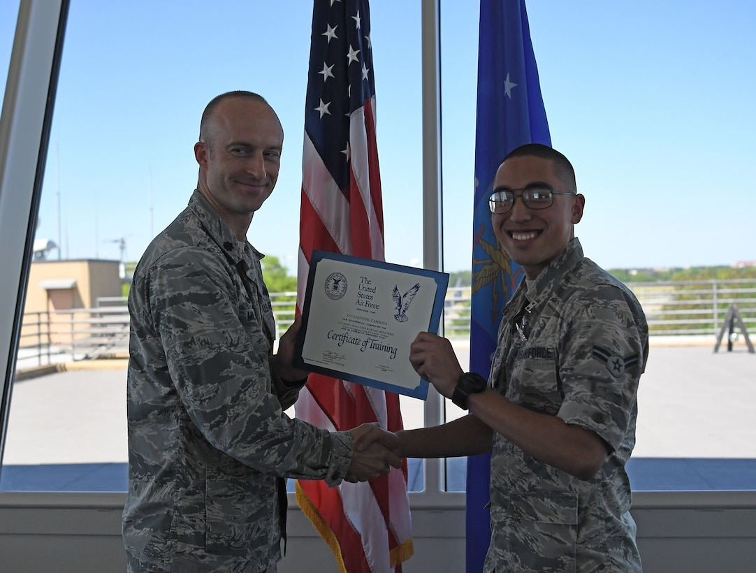 Lt. Col. Andrew Miller, 333rd Training Squadron commander, awards Airman 1st Class Josephino Cambosa, 333rd TRS student, a certificate of training for completing the Cyber Warfare Operations course on Keesler Air Force Base, Mississippi, April 10, 2019. Cambosa is the first non-prior service Airman to graduate from the Cyber Warfare Operations school house. (U.S. Air Force photo by 2nd Lt. Anh T. Bui)