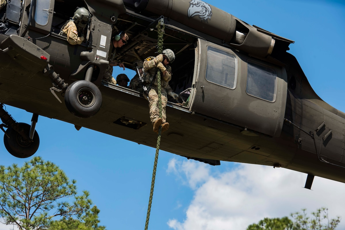 An airman slides down a rope from a helicopter.