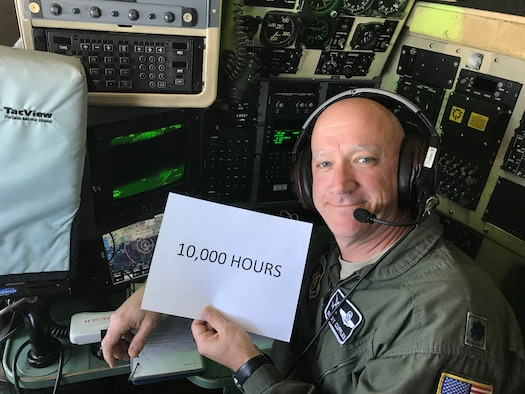 "Lt. Col. Barry ""JR"" Cupples, a navigator with the 757th Airlift Squadron, holds a 10,000 hours sign in the flight deck of a C-130H Hercules aircraft for a photo at the exact moment he completed his ten thousandth C-130 flight hour."