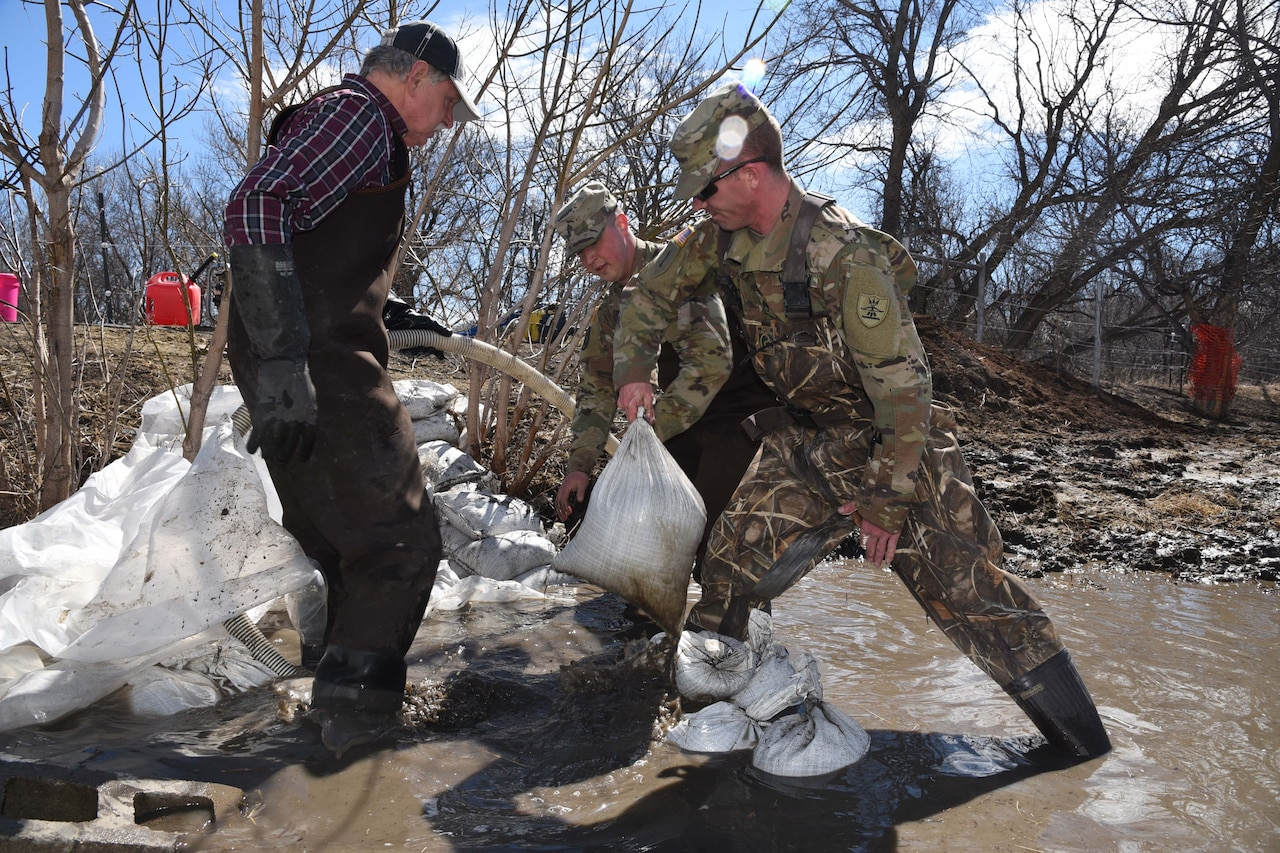 Service members build sand bags.