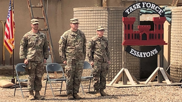 Capt. Joe Marut, Col. Jim Riely and Capt. Andrea Taylor stand at attention during a Change of Command Ceremony at Camp Taji, Iraq, April 6, 2019. Marut relinquished command of the Task Force Essayons (TFE) Headquarters Detachment to Taylor. Riely, the TFE commander, presided over the ceremony.