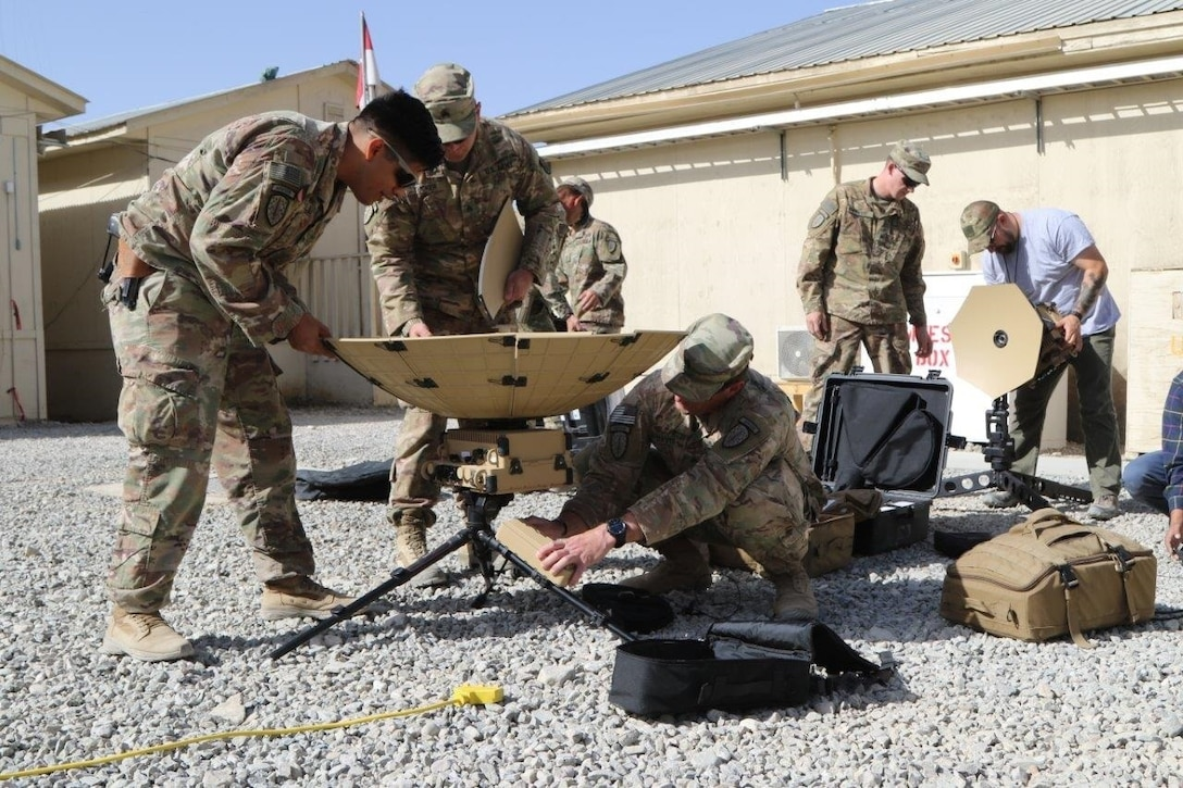 Service members train with satellite communication equipment.