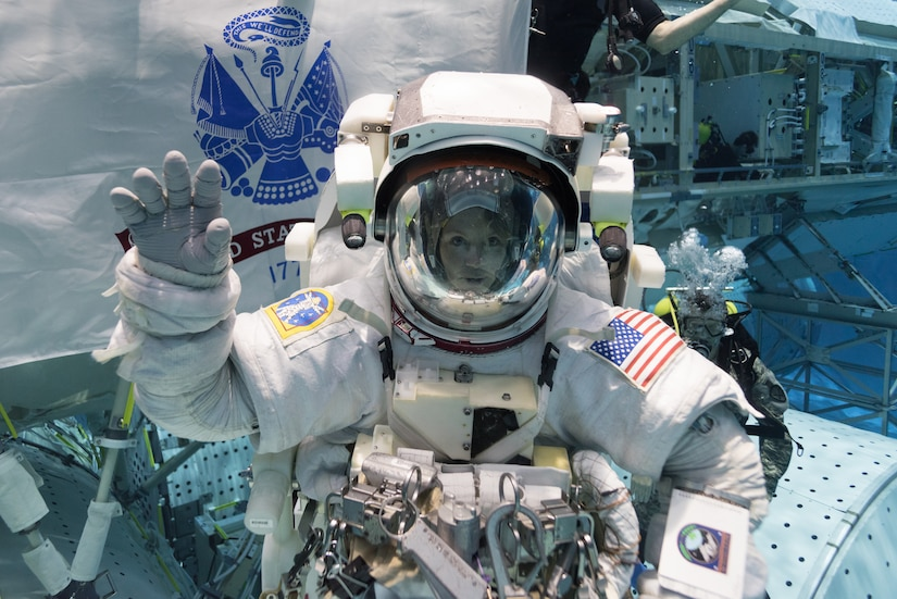 Astronaut in space suit raises her right hand.