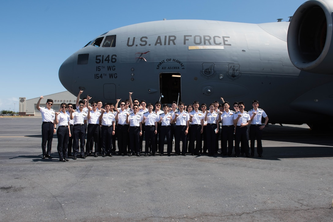 A group of Republic of Korea Air Force academy cadets take a group photo in front of a United States Hawaii Air National Guard C-17 Globemaster III during a visit to Joint Base Pearl Harbor-Hickam, Hawaii, Apr. 2, 2019.
