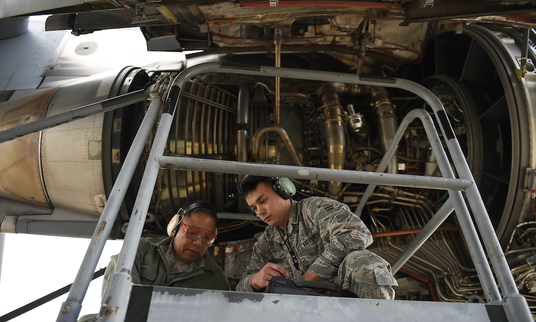 Master Sgt. Ruel Lechadores, 446th Aircraft Maintenance Squadron crew chief, and Airman 1st Class Ryan Watts, 62nd AMXS crew chief, communicate and work to repair an engine on a C-17 Globemaster
