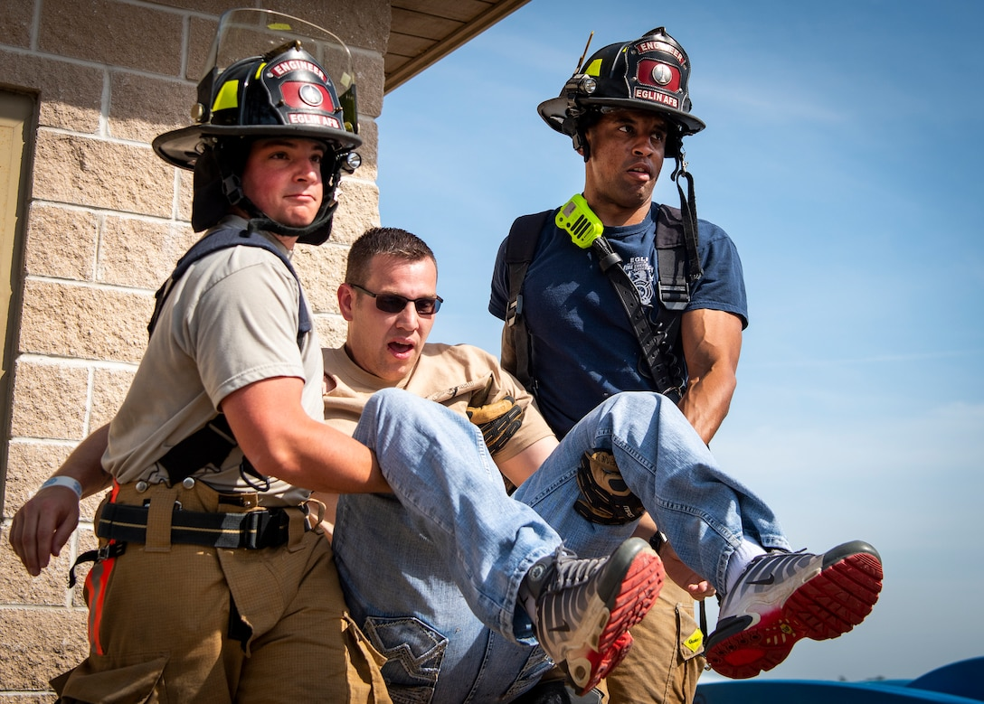 Firefighters carry an explosion victim to safety during an exercise at Eglin Air Force Base, Florida, April 3, 2019. Team Eglin held a two-day base readiness exercise that included force protection conditions, a fuel spill, explosion and active assailant scenarios. (U.S. Air Force photo by Samuel King Jr.)
