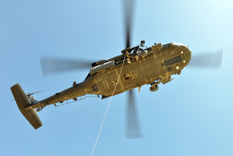 An Army National Guard UH-60 Blackhawk helicopter crew prepares to hoist Air Force pararescuemen from the 64th Expeditionary Rescue Squadron during joint training at Kandahar Airfield, Afghanistan, April 5, 2019. The rescue Airmen and Soldiers work and train together regularly to be prepared to save lives across the region. (U.S. Air Force photo by Capt. Anna-Marie Wyant)