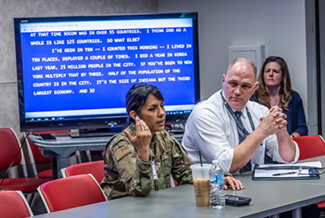 Military woman sits next to civilian man both in front of a blue screen tv with text