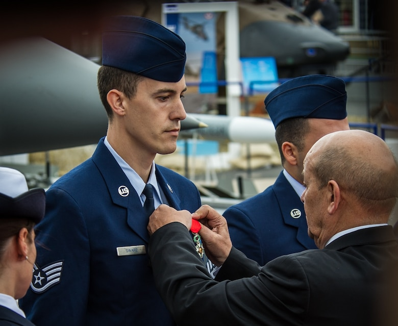 French Minister of Defence Jean Yves Le Drian pins the French Legion of Honor Medal on Staff Sgt. Greggory Swarz at Le Bourget Airport during the International Paris Air Show, June 15, 2015. Swarz was recognized for his heroic actions on Jan. 26, 2015, when he saved the lives of three French airmen after a Hellenic air force F-16 Fighting Falcon crashed into the parking ramp at Los Llanos Air Base, Spain, during Tactical Leadership Program 15-1. (U.S. Air Force photo/ Tech. Sgt. Ryan Crane)