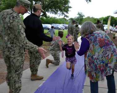 """Joint Base San Antonio leaders, service members, teachers and school administrators greeted Fort Sam Houston Elementary School students before classes for """"Purple Up! For Military Kids"""" day April 12. JBSA and San Antonio community members were encouraged to wear purple to recognize military children for their personal sacrifice and courage in supporting their military parents. The children were given purple beads by service members as they made their way to school. """"Purple Up! For Military Kids"""" day commemorated the Month of the Military Child in April, which acknowledges the important role of military children and families worldwide in the armed forces, acknowledging the sacrifices they make and the challenges they overcome on a daily basis."""