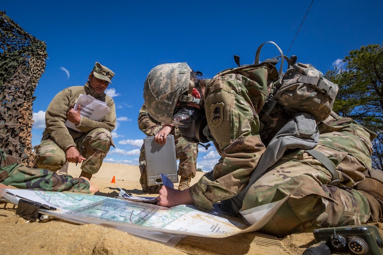 A group of soldiers kneel together in the sand as one of them looks through some papers.