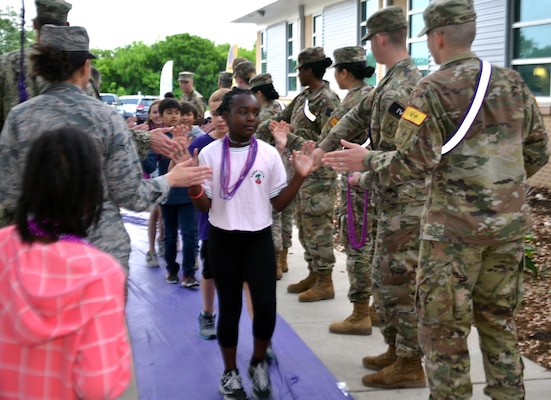 "Joint Base San Antonio leaders, service members, teachers and school administrators greeted Fort Sam Houston Elementary School students before classes for ""Purple Up! For Military Kids"" day April 12. JBSA and San Antonio community members were encouraged to wear purple to recognize military children for their personal sacrifice and courage in supporting their military parents. The children were given purple beads by servicemembers as they made their way to school. ""Purple Up! For Military Kids"" day commemorated the Month of the Military Child in April, which acknowledges the important role of military children and families worldwide in the armed forces, acknowledging the sacrifices they make and the challenges they overcome on a daily basis."