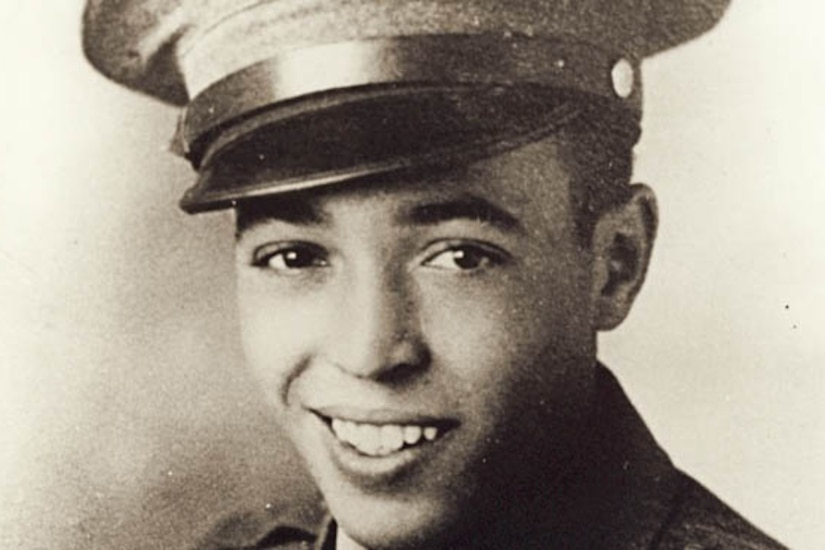 A Marine in his dress cap smiles.