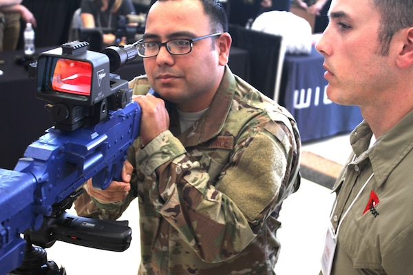 Master Sgt. Juan De La Rosa listens to a presentation on a any-light weapon aiming system at Industry Day April 9 at Joint Base San Antonio-Lackland. Several dozen vendors set up booths at the event to show installation and mission support Airmen and visiting senior Air Force leaders the latest equipment and technology available to potentially help the Air Force as it continues to defend the United States.