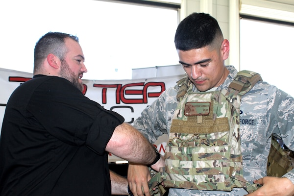 Staff Sgt. Eric Martinez tries on a quick-release protection vest during Industry Day April 9 at Joint Base San Antonio-Lackland. Several dozen vendors set up booths at the event to show installation and mission support Airmen and visiting senior Air Force leaders the latest equipment and technology available to potentially help the Air Force as it continues to defend the United States.