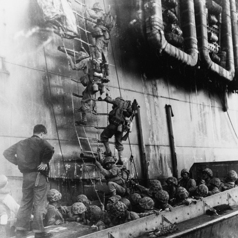 Marines climb down a net on the side of a ship into a small boat filled with more Marines.