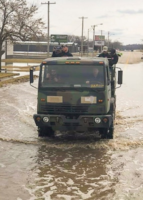 Lewis Sieber, fire equipment manager of the Nebraska Forest Service navigates through flood water searching for stranded people in a six-wheeled drive cargo truck issued through the DoD Firefighter Program. Photo provided by the Nebraska Forest Service