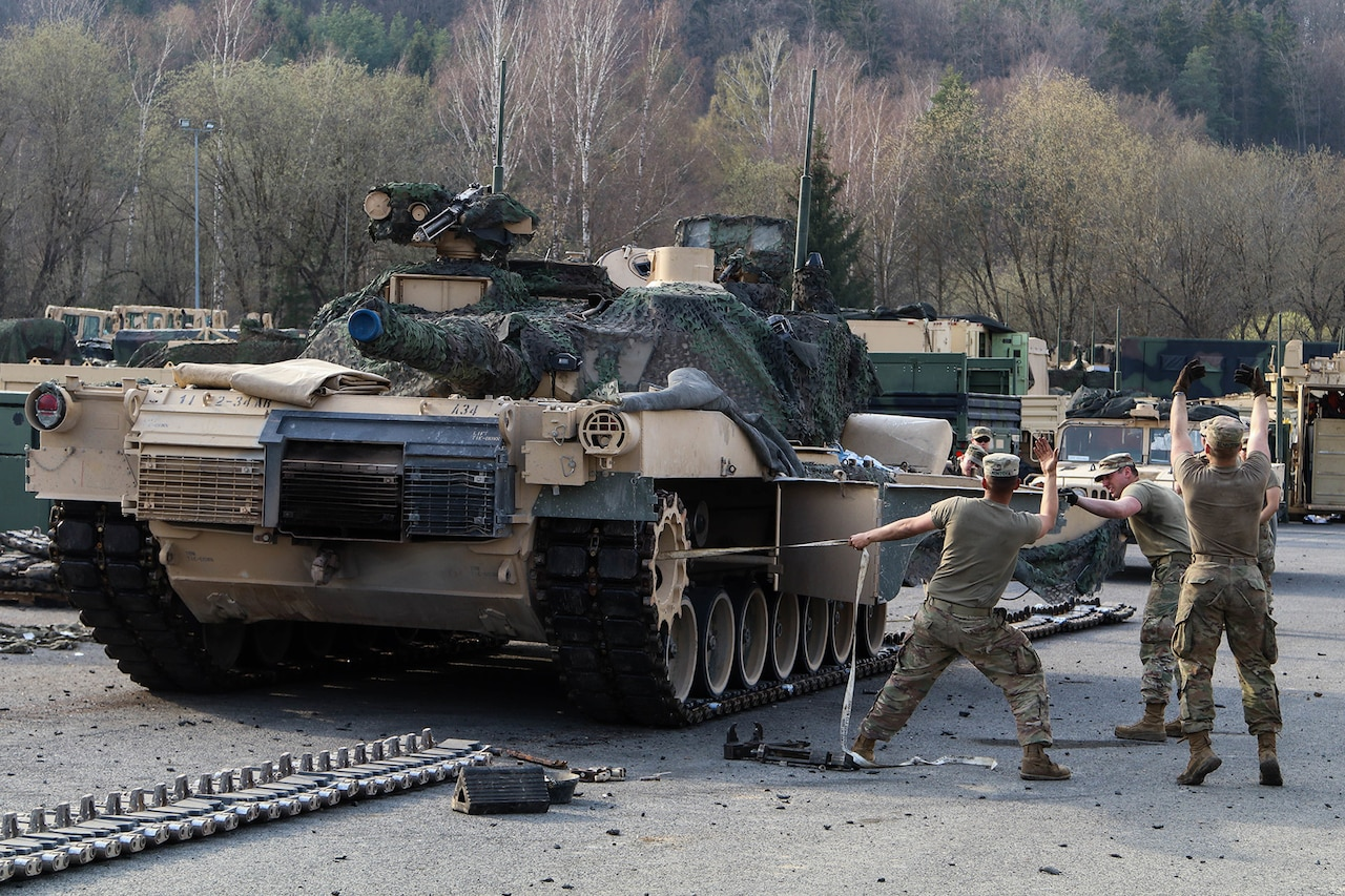 Soldiers perform maintenance on tanks.