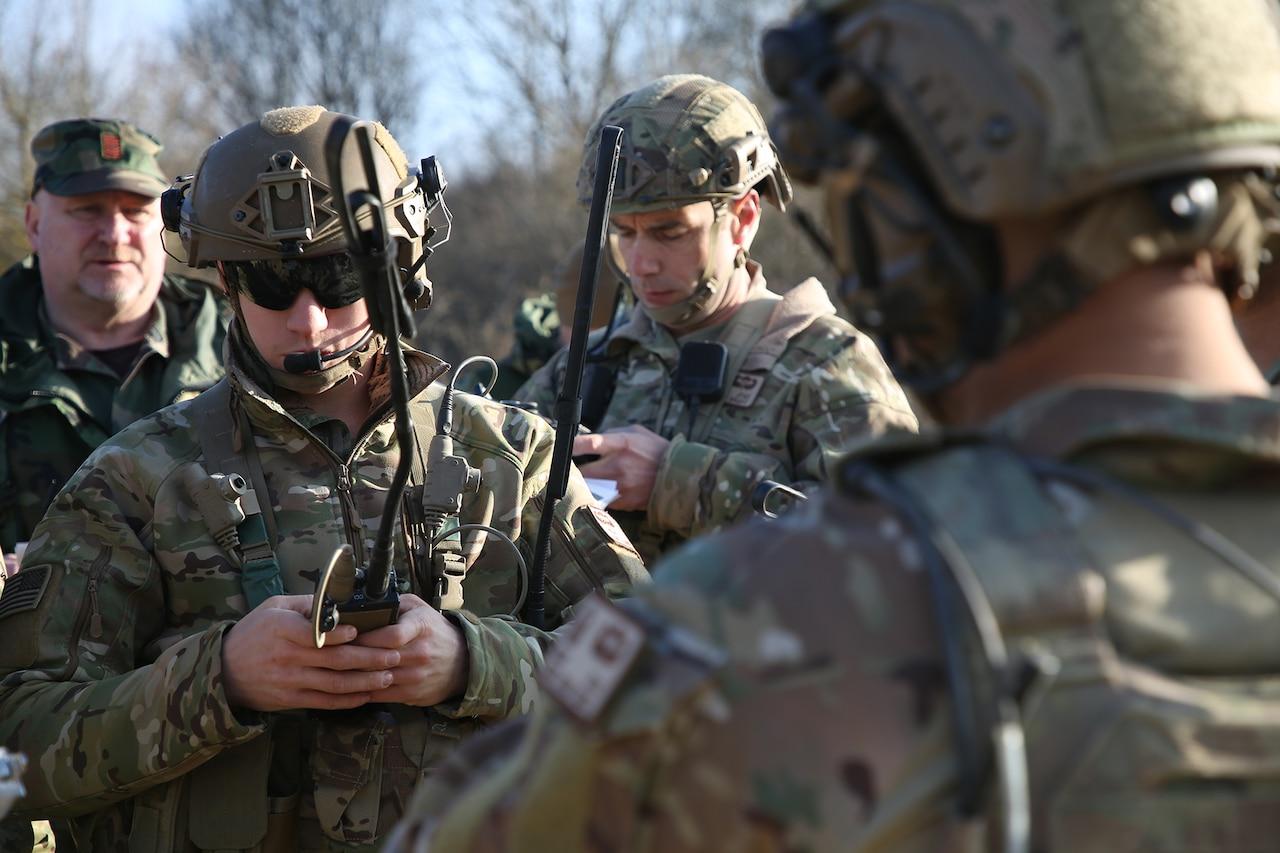 Soldiers look at radios.