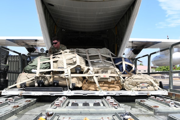 U.S. Air Force Staff Sgt. Drayton Callen, 81st Logistics Readiness Squadron deployment training NCO in charge, unloads cargo off of a U.S. Coast Guard HC-130J in support of exercise Neptune Guardian on Keesler Air Force Base, Mississippi, April 5, 2019. The 81st LRS acted as a one-stop shop for ground and air transportation as well as munition requirements for joint exercise Neptune Guardian between the U.S. Coast Guard and U.S. Navy. (U.S. Air Force photo by Senior Airman Suzie Plotnikov)