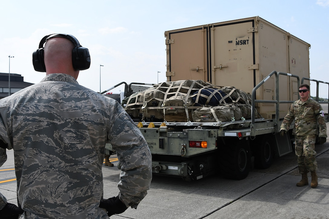 U.S. Air Force Tech. Sgt. Brian Teachout, 81st Logistics Readiness Squadron Small Air Terminal NCO in charge, and Staff. Sgt. Drayton Callen, 81st LRS deployment training NCO in charge, wait for a forklift to unload cargo in support of exercise Neptune Guardian on Keesler Air Force Base, Mississippi, April 5, 2019. The 81st LRS acted as a one-stop shop for ground and air transportation as well as munition requirements for joint exercise Neptune Guardian between the U.S. Coast Guard and U.S. Navy. (U.S. Air Force photo by Senior Airman Suzie Plotnikov)