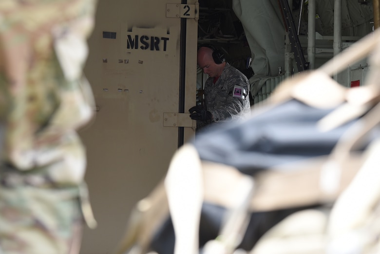 U.S. Air Force Tech. Sgt. Brian Teachout, 81st Logistics Readiness Squadron Small Air Terminal NCO in charge, unloads cargo off of a U.S. Coast Guard HC-130J in support of exercise Neptune Guardian on Keesler Air Force Base, Mississippi, April 5, 2019. The 81st LRS acted as a one-stop shop for ground and air transportation as well as munition requirements for joint exercise Neptune Guardian between the U.S. Coast Guard and U.S. Navy. (U.S. Air Force photo by Senior Airman Suzie Plotnikov)