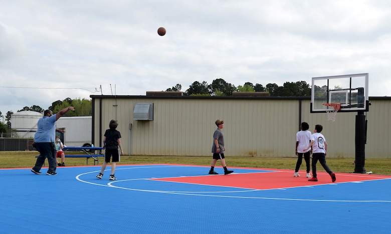 Andre Logan, 14th Force support Squadron, Child and Youth services Flight Chief, plays basketball with kids during the Youth Center's Month of the Military Child kickoff, April 5, 2019, on Columbus Air Force Base, Miss. As the month celebration continues, families will be able to participate in many activities, such as a Purple Up Day and a Movie on the Lawn April 12, a and Spring Fling April 20 which will feature egg hunts for various age ranges, face painting, petting zoo, games bounce castles and more (U.S. Air Force photo by Airman Hannah Bean)