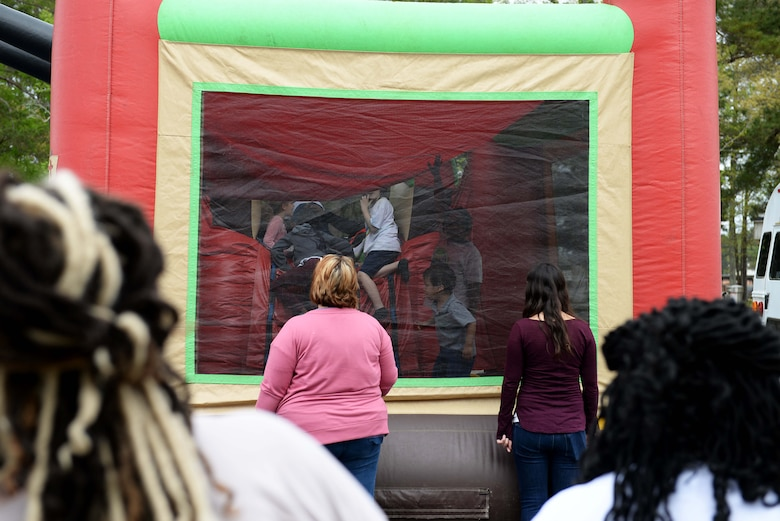 "Caregivers watch over kids playing in the bouncy castle during the Youth Center's Month of the Military Child kickoff, April 5, 2019, on Columbus Air Force Base, Miss. One major theme for the month of April is ""Purple Up"" , which is used as a way to show support and thank military youth for their strength and spirit. (U.S. Air Force photo by Airman Hannah Bean)"