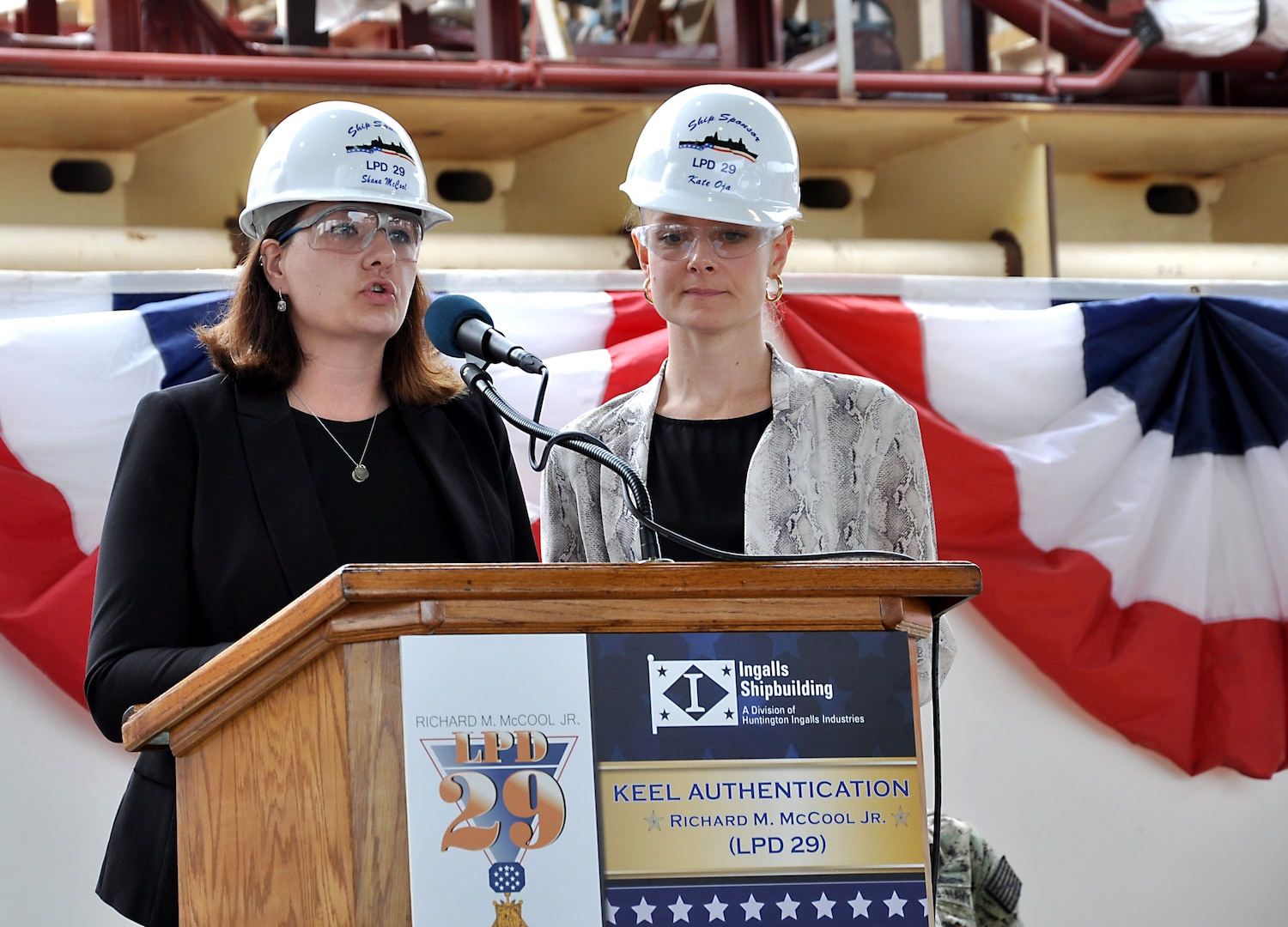 Shana McCool (left) and Kate Oja, ship sponsors of the future USS Richard M. McCool Jr. (LPD 29), speak about their grandfather during the keel authentication ceremony for the ship at Huntington Ingalls Industries Pascagoula shipyard April 12.
