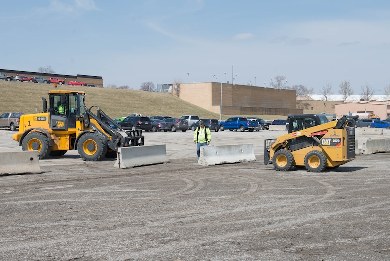 Members of the 55th Civil Engineer Squadron pavement and equipment team build the boundaries of a temporary parking lot exclusively for those who work in building 500 March 27, 2019, at Offutt Air Force Base, Nebraska. The temporary parking lot was established as part of the recovery from flooding on base that began March 15, 2019. (U.S. Air Force photo by Zachary Hada)