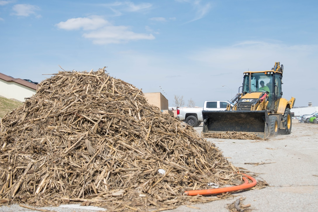 Charles Cswercko, 55th Civil Engineer Squadron pavement and equipment operator, clears flood debris near building 500 to build a temporary parking lot March 27, 2019, at Offutt Air Force Base, Nebraska. The 12 person pavement and equipment team is responsible for all pavement repair on the installation, in addition to snow removal. (U.S. Air Force photo by Zachary Hada)