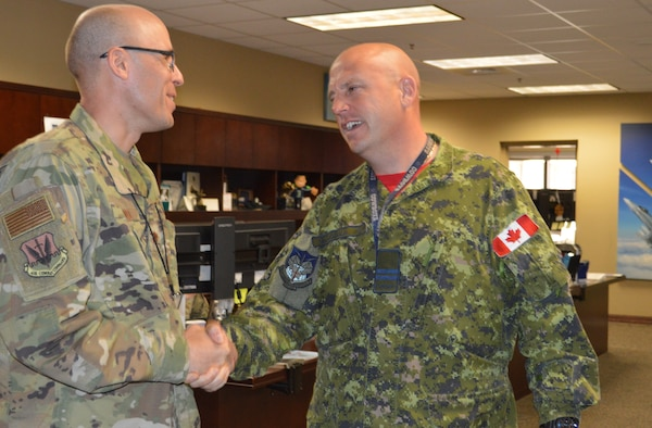 Chaplain (Maj.) Rudy Olivo, Component Numbered Air Force Chaplain, Continental U.S. NORAD Region-1st Air Force (Air Forces Northern), is congratulated by Royal Canadian Air Force Capt. Charles MacDonald, on Olivo's selection as the 2018 Samuel Stone Award, Air National Guard Chaplain of the Year. (U.S. Air Force photo by Mary McHale)