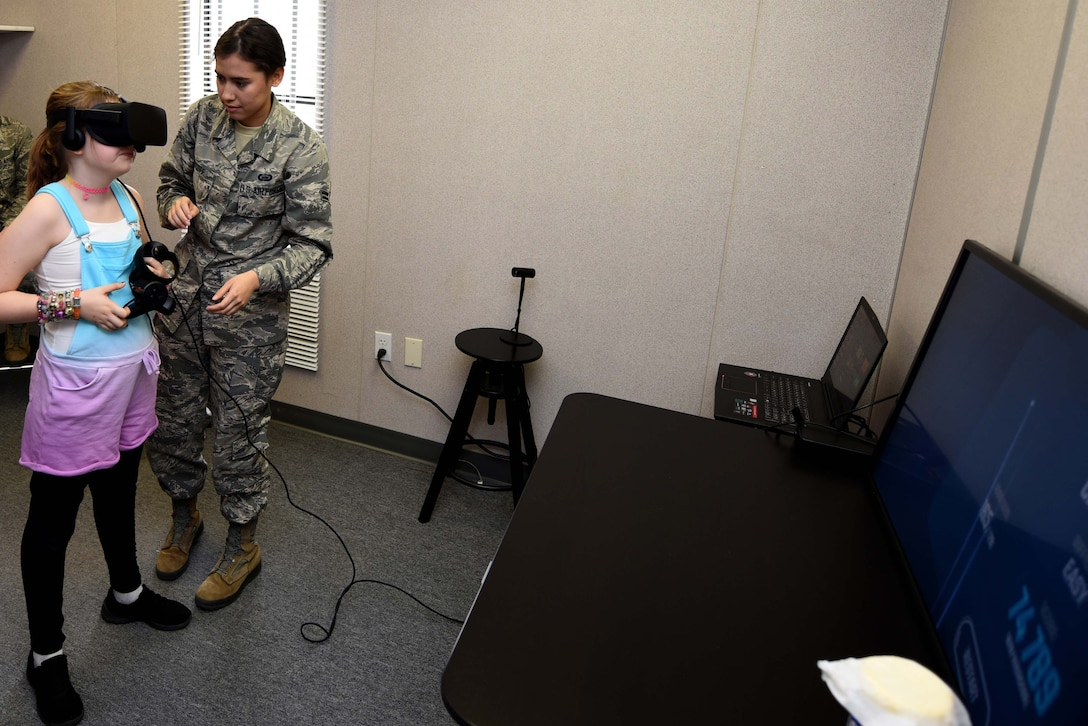 U.S. Air Force Airman 1st Class Annabell, 548th Intelligence, Surveillance and Reconnaissance Group, assists Catie an event attendee, with setting up the virtual reality station at the Innovation Lab during the 548th ISR Group's annual open house at Beale Air Force Base, California, April 3, 2019. Tours, briefings and demonstrations during the event gave attendees an inside look at the important work their Airmen do. (U.S. Air Force photo by Airman 1st Class Michael Richmond)