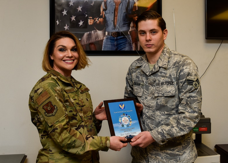 U.S. Air Force Senior Airman Justin Porter, 377th Maintenance Squadron munition operations technician, receives the March Diamond Sharp award from Master Sgt. Robbie Powell-Greenwood, 377th MXS acting first sergeant, at Kirtland Air Force Base, N.M., April 12, 2019. Porter worked directly with the 58th Special Operations Wing plans and scheduling section and correctly calculated requirements for 40 aircraft and coordinated the delivery of over 1.5 million munitions, fulfilling the demands of a $2.4 billion fleet. This resulted in 112 successful combat search and rescue training sorties and the certification of 166 Special Warfare (Battlefield) Airmen. (U.S. Air Force photo by Airman 1st Class Austin J. Prisbrey)
