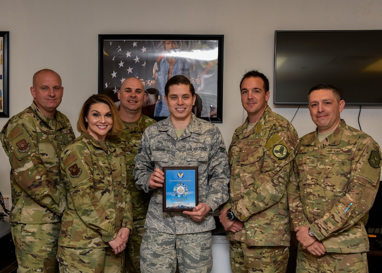 U.S. Air Force Senior Airman Justin Porter (center), and members of Team Kirtland First Sergeants pose for a photo at Kirtland Air Force Base, N.M., April 12, 2019. Porter worked directly with the 58th Special Operations Wing plans and scheduling section and correctly calculated requirements for 40 aircraft and coordinated the delivery of over 1.5 million munitions, fulfilling the demands of a $2.4 billion fleet. This resulted in 112 successful combat search and rescue training sorties and the certification of 166 Special Warfare (Battlefield) Airmen. (U.S. Air Force photo by Airman 1st Class Austin J. Prisbrey)