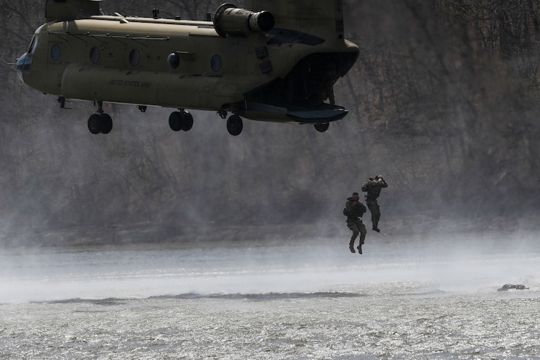 Two soldiers jump from a helicopter into a lake.