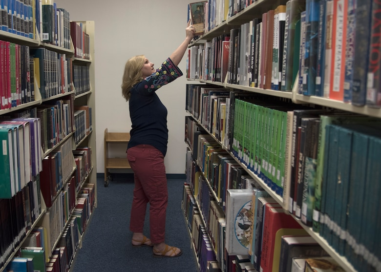 Jennifer Crowell, 56th Force Support Squadron library director, shelves a book April 8, 2019, at Luke Air Force Base, Ariz.