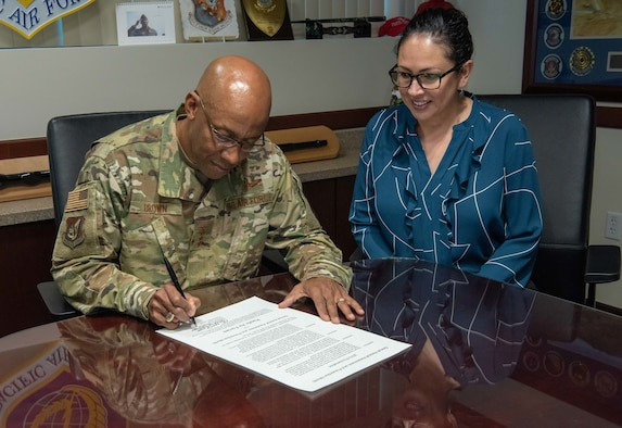 Gen. CQ Brown, Jr., Pacific Air Forces commander, signs a Sexual Assault Awareness and Prevention Month proclamation alongside Dr. Lisa Charles, Pacific Air Forces Sexual Assault Prevention and Response program manager, at Joint Base Pearl Harbor-Hickam, Hawaii, Mar. 11, 2019.