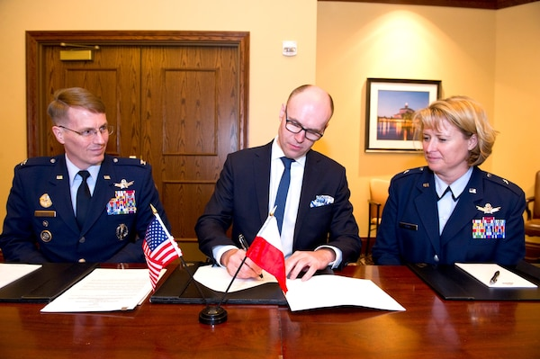 Michal Szaniawski, acting president of the Polish Space Agency, signs an agreement for space situational awareness (SSA) services and data as U.S. Space representative U.S. Air Force Col. Christopher Eagan (left), chief of Policy Division, U.S. Strategic Command (USSTRATCOM), and U.S. Air Force Brig. Gen.  Deanna Burt, director of Operations and Communications, U.S. Air Force Space Command, witnessed the signing. Szaniawski signed the agreement as part of a larger effort to support spaceflight planning and enhance the safety, stability and sustainability of space operations. Poland joins 18 nations, two intergovernmental organizations, and 77 commercial satellite owners, operators, launchers already participating in SSA data-sharing agreements with USSTRATCOM.