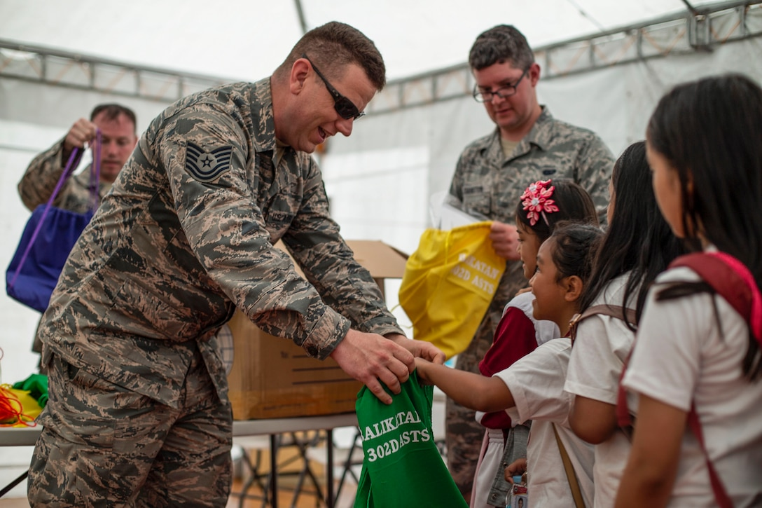 A smiling airman passes a bag to a student, who smiles up at him.